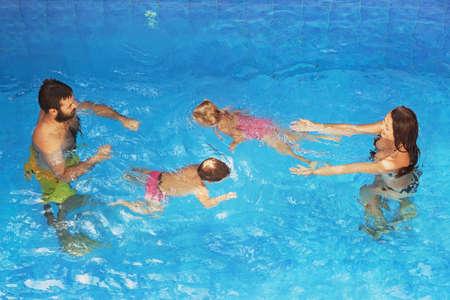 Happy family - père et la mère dans la piscine bleu avec des bébés fille et garçon nage sous-marine avec plaisir. Mode de vie sain, les parents et les personnes actives eau des cours de sport sur les vacances d'été avec les enfants