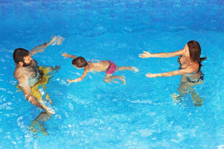 recreational sports: Happy family - father and mother in pool with baby boy swimming underwater with fun. Healthy lifestyle, active parents and people water sports recreational activity on summer holidays with children Stock Photo
