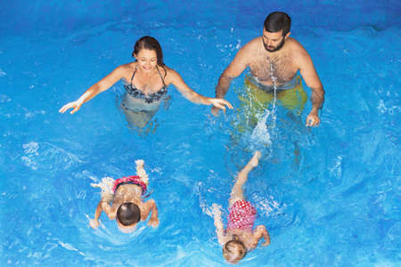 sport training: Happy family - father and mother in blue pool with babies girl and boy swimming underwater with fun. Healthy lifestyle, active parents and people water sports activity on summer vacation with children Stock Photo