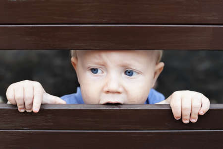 Portrait of abandoned by parents little baby boy with staring blue eyes, sad and lonely face expression, looking out through the fence. Social family problems and children stress and negative emotions