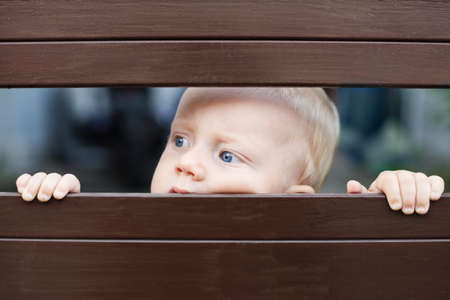 looking at baby: Portrait of abandoned little baby boy with staring blue eyes, sad and lonely face expression, looking out through fence and waiting for parents. Family relationships, children feelings and emotions