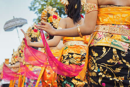 dancer: Group of beautiful Balinese girls in bright traditional costumes - sarongs decorated by hindu Barong and Garuda masks. Arts and culture of Bali island and Indonesia people and asian travel backgrounds