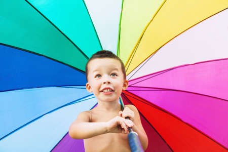 multi colors: Face portrait of smiling cheerful baby boy having a fun and turning umbrella with bright colorful pattern. Family healthy lifestyle, children positive emotions and images of multi colors objects