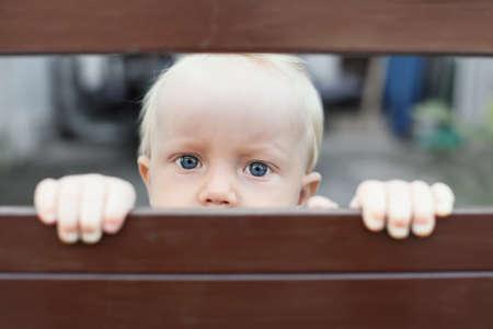 Portret van de steek gelaten door de ouders van de baby jongen met blauwe ogen staren, verdrietig en eenzaam gezichtsuitdrukking, die uit door hek. Sociale problemen, familie misbruik, kinderen stress en negatieve emoties