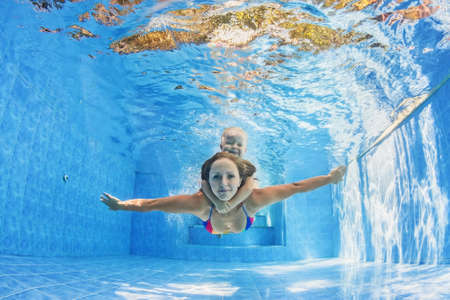 Happy family - positive mother with baby girl swimming and diving underwater with fun in outdoor pool. Healthy lifestyle, active parents, and people water sports activity on summer holidays with child Stock Photo