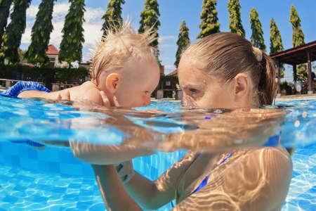 Portret van jongen plezier in het zwembad met blijde moeder. Gezonde leefstijl, watersport activiteiten, baby zwemmen en duiken onderwater lessen met actieve ouders op zomervakantie met kinderen