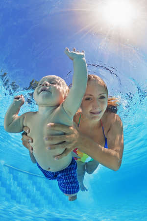 Happy family - positive mother with baby boy swim underwater and dive with fun in blue outdoor pool. Healthy lifestyle, active parents and people water sports activity on summer holidays with children Stock Photo