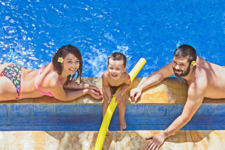 Happy family - father and mother with baby son relax with fun after diving underwater and children swimming lesson in outdoor pool. Active parents, and people water sports activity on summer holidays