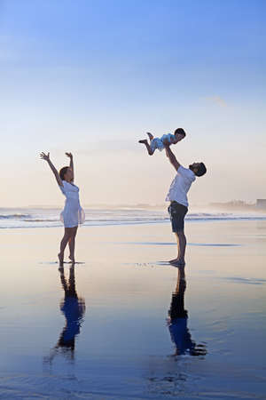 Positive family - father, mother with baby son relax with fun on smooth black sand sea beach. Healthy lifestyle, active parents, and people outdoor activity on tropical summer holidays with children