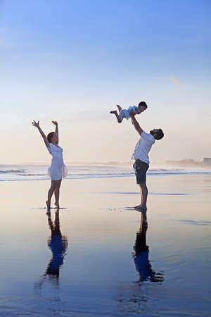 Positiv familje - far, mor med baby son koppla av med kul på slät svart sand stranden. Hälsosam livsstil, aktiva föräldrar och människor utomhus aktivitet på tropiska sommarlovet med barn