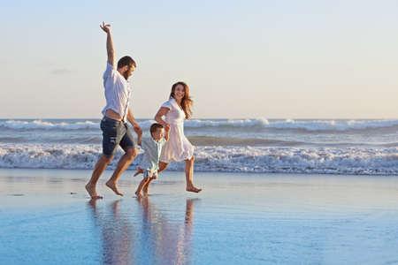 familia: Familia positiva - padre, madre con el hijo del bebé toman de las manos y correr con diversión en el borde del mar en la playa de arena suave. Los padres y la gente Activo actividad al aire libre en las vacaciones tropicales de verano con niños