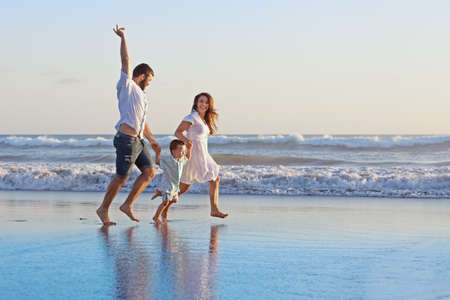 Positive family - father, mother with baby son hold hands and run  with fun along edge of sea on smooth sand beach. Active parents and people outdoor activity on tropical summer holidays with children