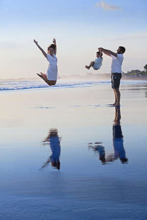 summer holidays: Positive family - father, mother with baby son walk with fun on smooth black sand sea beach. Healthy lifestyle, active parents, and people outdoor activity on tropical summer holidays with children
