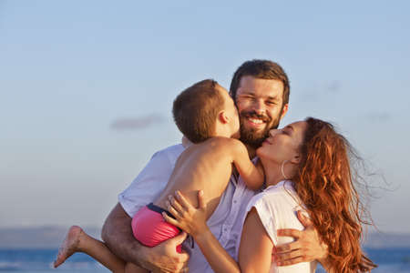 Portret van positieve familie - gelukkige moeder en vader bedrijf baby zoon op handen lopen met plezier op zee zand strand. Actieve ouders en mensen outdoor activiteiten op tropische zomer vakantie met kinderen