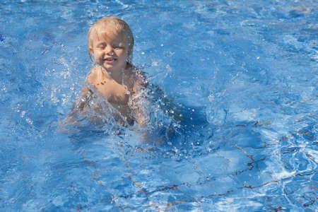 personas saltando: Bebé sonriente feliz tiene saltando divertirse con las salpicaduras de agua azul en la piscina antes de las clases de natación. Estilo de vida saludable, los padres activos, y la actividad de los deportes la gente el agua en familia de vacaciones de verano con el bebé.