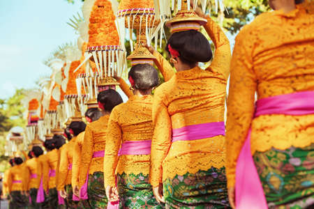 indonesia: Procession of beautiful Balinese women in traditional costumes - sarong, carry offering on heads for Hindu ceremony. Arts festival, culture of Bali island and Indonesia people, Asian travel background