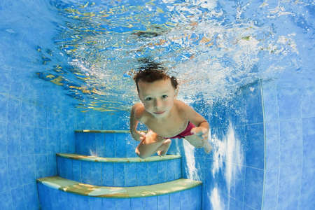 actividades recreativas: Nadar con diversión Niño sonriente - salto submarina y buceo en la piscina al aire libre. Estilo de vida familiar saludable, actividad deportiva de agua y ejercicios físicos con padres activos en vacaciones de verano con bebé