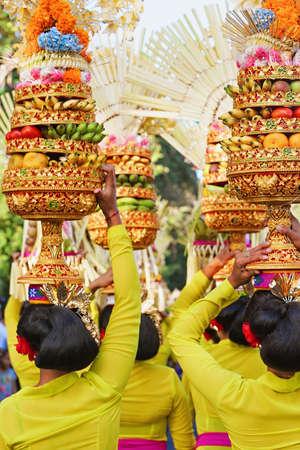 Procession av vackra balinesiska kvinnor i traditionella dräkter bär rituella erbjudanden på huvudet för hinduisk ceremoni. Konstfestivalen, kultur Bali människor, och Indonesien öar. Asiatisk rese bakgrund Stockfoto