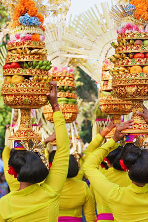 indonesia people: Procession of beautiful Balinese women in traditional costumes carry ritual offerings on heads for Hindu ceremony. Arts festival, culture of Bali people, and Indonesia islands. Asian travel background Stock Photo