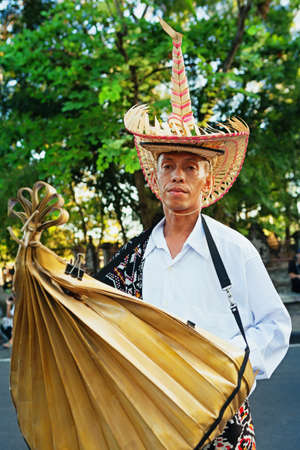 BALI, INDONESIA - JUNE 13: Portrait of Nusa Tenggara man in traditional straw hat of Rote island people with musical instrument Sasando at Bali arts and culture festival. Denpasar, Bali 13 June, 2015