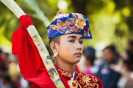BALI, INDONESIA - JUNE 13: Portrait of Bali man in beautiful Balinese people costume with traditional style face make-up on parade at Bali arts and culture festival in Denpasar, Bali, 13 June, 2015