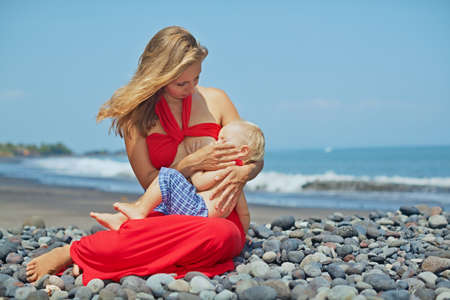 Beautiful portrait of happy mother in red dress sitting on sea beach and breast feeding small baby son. Healthy lifestyle, active parents, and positive emotions on summer family vacation with children