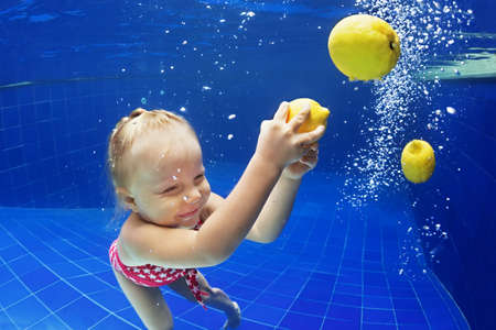 citrus family: Children swimming lesson - little baby girl jump and dive underwater in pool with fun for lemon fruit. Active healthy lifestyle, water sports activity and exercising with parents on family vacation.