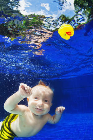 Children swimming lesson - little baby boy dive underwater in pool with fun for yellow duck toy. Active healthy lifestyle, water sport activity and exercising with parents on family vacation with son.