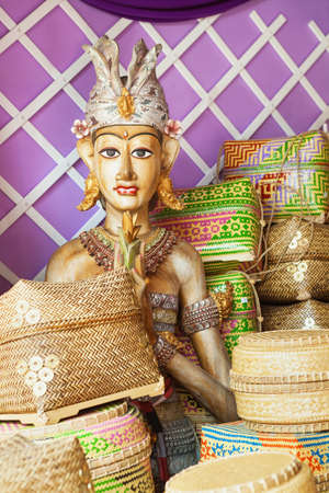 art and craft: Colored balinese man figure in traditional costume and ceremonial bamboo boxes for hindu offering. Arts, religion and culture festivals of Indonesian and Bali island people. Asian travel backgrounds.