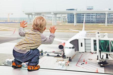 Liten pojke v�ntar ombordstigning flygning i flygplatstransithallen och tittar in genom f�nstret p� flygplan n�ra gaten. Aktiv familj livsstil, resor med flyg med barn p� semester