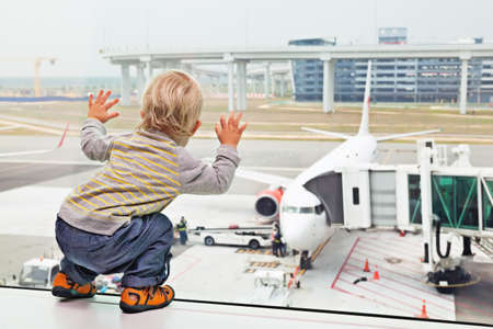departure board: Little baby boy waiting boarding to flight in airport transit hall and looking through the window at airplane near departure gate. Active family lifestyle, travel by air with child on summer vacation