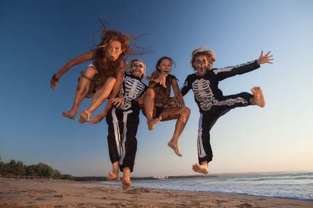 Grupp unga tjejer i skrämmande skelett och vilda viljiga kostymer hoppar högt i luften med roligt före Halloween nattfest på solnedgången på havet. Aktiva människor, livsstilar och evenemangsfester på semester