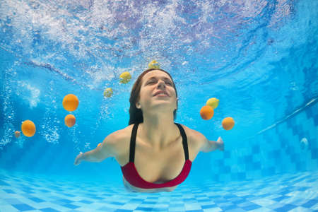 Young beautiful woman in bikini swimming and diving underwater in pool with fun for fresh citrus fruit. Active healthy lifestyle, water sport activity and relaxation on vacation in tropical spa resort 스톡 콘텐츠