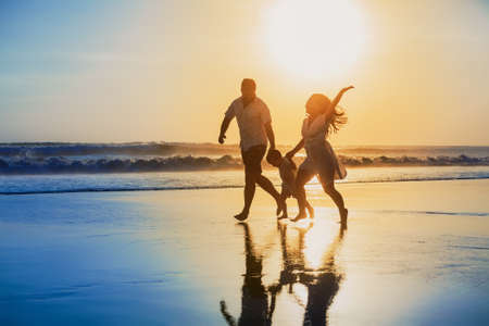 tropical sunset: Happy family - father, mother, baby son hold hands and run with fun along edge of sunset sea on black sand beach. Active parents and people outdoor activity on tropical summer vacations with children