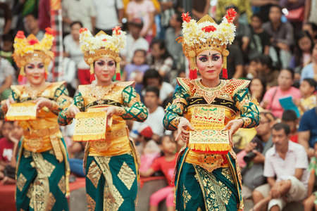 culture: BALI, INDONESIA - JUNE 28, 2015: Beautiful women group dressed in colorful sarongs - Balinese style female dancer costume, dancing traditional temple dance Legong at Bali Art and Culture Festival show