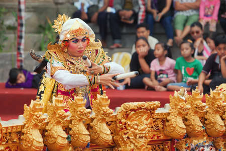 male costume: BALI, INDONESIA - JUNE 28, 2015: Musician and dancer man dressed in Balinese style male costume dancing and playing music on the traditional musical instrument Gamelan at Art and Culture Festival show Editorial