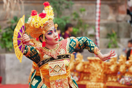 indonesia: BALI ISLAND, INDONESIA - JUNE 28, 2015: Beautiful woman dressed in colorful sarong - Balinese style female dancer costume, dancing traditional temple dance Legong at Bali Art and Culture Festival show