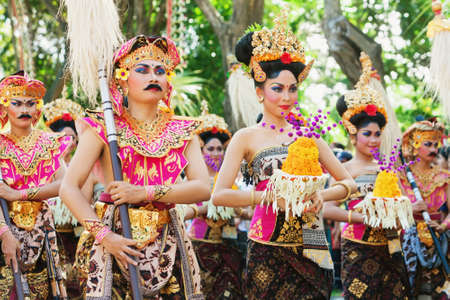 traditional costume: BALI, INDONESIA - JUNE 13, 2015: Beautiful women and men dancers group dressed in colorful sarongs - Balinese style costume, dancing traditional temple dance at Bali Art and Culture Festival show. Editorial