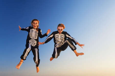 weekend activities: Two young girls in scary skeleton costumes jumping high in air with fun before Halloween night party on sunset sea beach. Active people, lifestyles and event celebrations on holidays