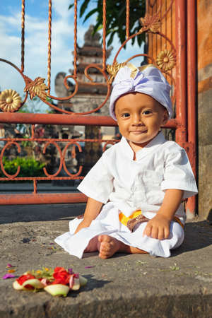 traditional costume: Portrait of balinese baby boy with smiling face in traditional costume Sarong sitting in hindu temple at religious ceremony. Bali island children lifestyle and national culture of Indonesian people. Stock Photo