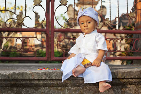 ceremonial clothing: Portrait of balinese baby boy with smiling face in traditional costume Sarong sitting in hindu temple at religious ceremony. Bali island children lifestyle and national culture of Indonesian people. Stock Photo