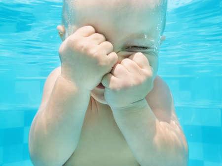 작은 아기 소년 수영 수영장에서 재미와 다이빙 수중의 재미 얼굴 초상화입니다. 활성 건강 한 라이프 스타일, 수상 스포츠 활동과 아이들과 함께 가족