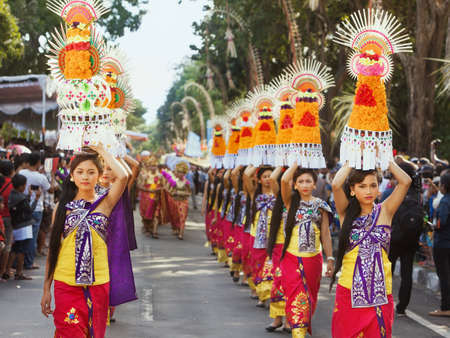 ethnicity: DENPASAR, BALI ISLAND, INDONESIA - JUNE 13, 2015: Group of beautiful women dressed in traditional Balinese costumes carry on head religious offering for hindu ceremony on parade at Bali Art Festival. Editorial