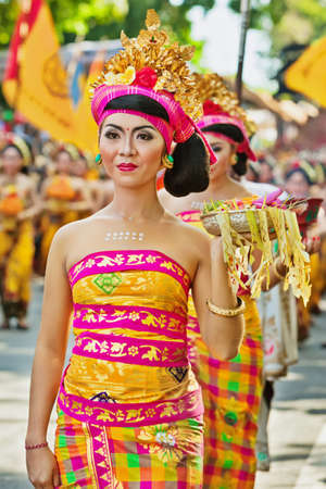 ceremonial clothing: DENPASAR, BALI ISLAND, INDONESIA - JUNE 13, 2015: Beautiful woman dressed in traditional Balinese costume - sarong carrying religious offering for hindu ceremony on parade at Bali Art Festival. Editorial
