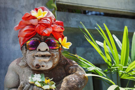 funny people: Humorous face portrait of old traditional Balinese temple guard statue dressed in funny tourist costume with sunglasses Arts, culture of Bali and Indonesian people and asian vacation travel background