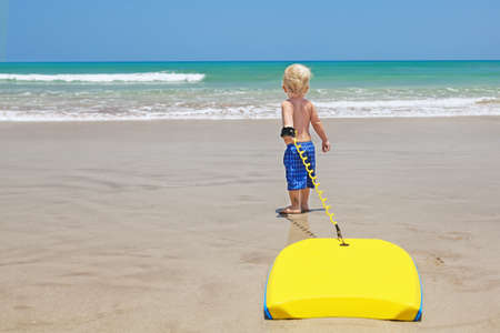 Little baby boy - young surfer with bodyboard has a fun on sea sand beach. Active family lifestyle, people outdoor water sport lessons and swimming activity on surf camp summer vacation with child.