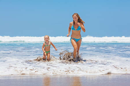 daughter: Happy family - mother and small baby daughter swim with fun in sea surf and run with splashes to black sand beach. Active parents and people outdoor activity on tropical summer vacations with child.