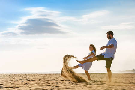 husband: Happy newlywed family on honeymoon holidays - just married loving wife and husband run with fun on sea sand beach. Active lifestyle and people outdoor activity on summer vacation on tropical island. Stock Photo