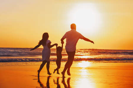 Happy family - father, mother, baby son hold hands and run with fun along edge of sunset sea on black sand beach. Active parents and people outdoor activity on tropical summer vacations with children. Stock Photo
