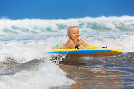 bodyboarder: Little baby girl - young surfer with bodyboard has a fun on small sea waves. Active family lifestyle, people outdoor water sport lessons and swimming activity on surf camp summer vacation with child.